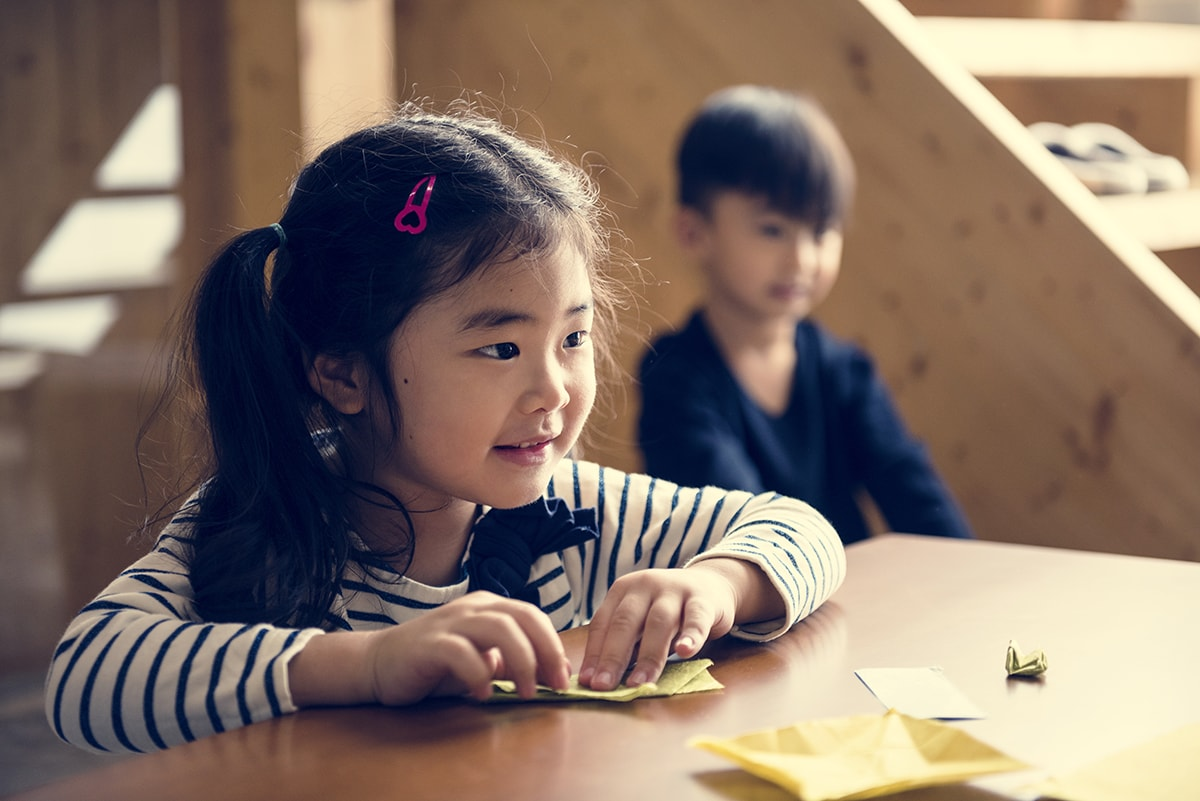 Little girl folding origami