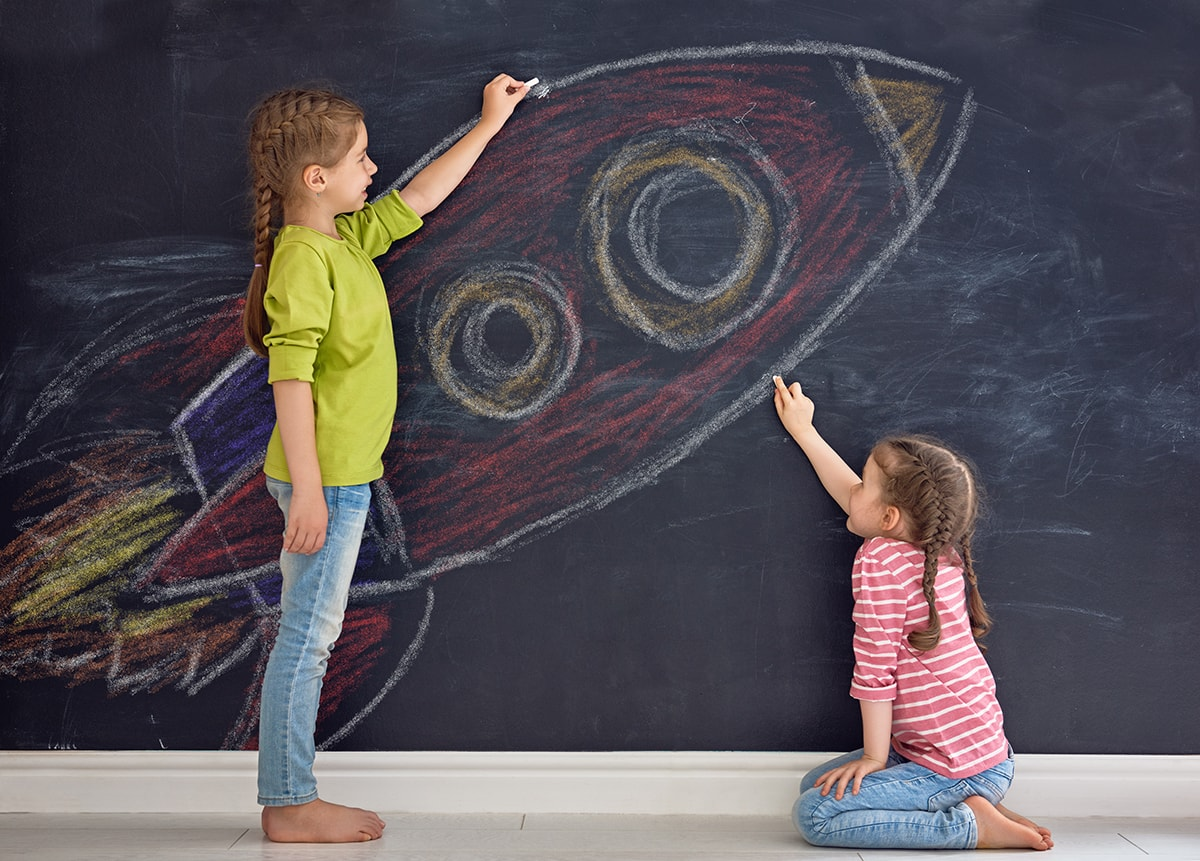Children drawing rocket ship on blackboard