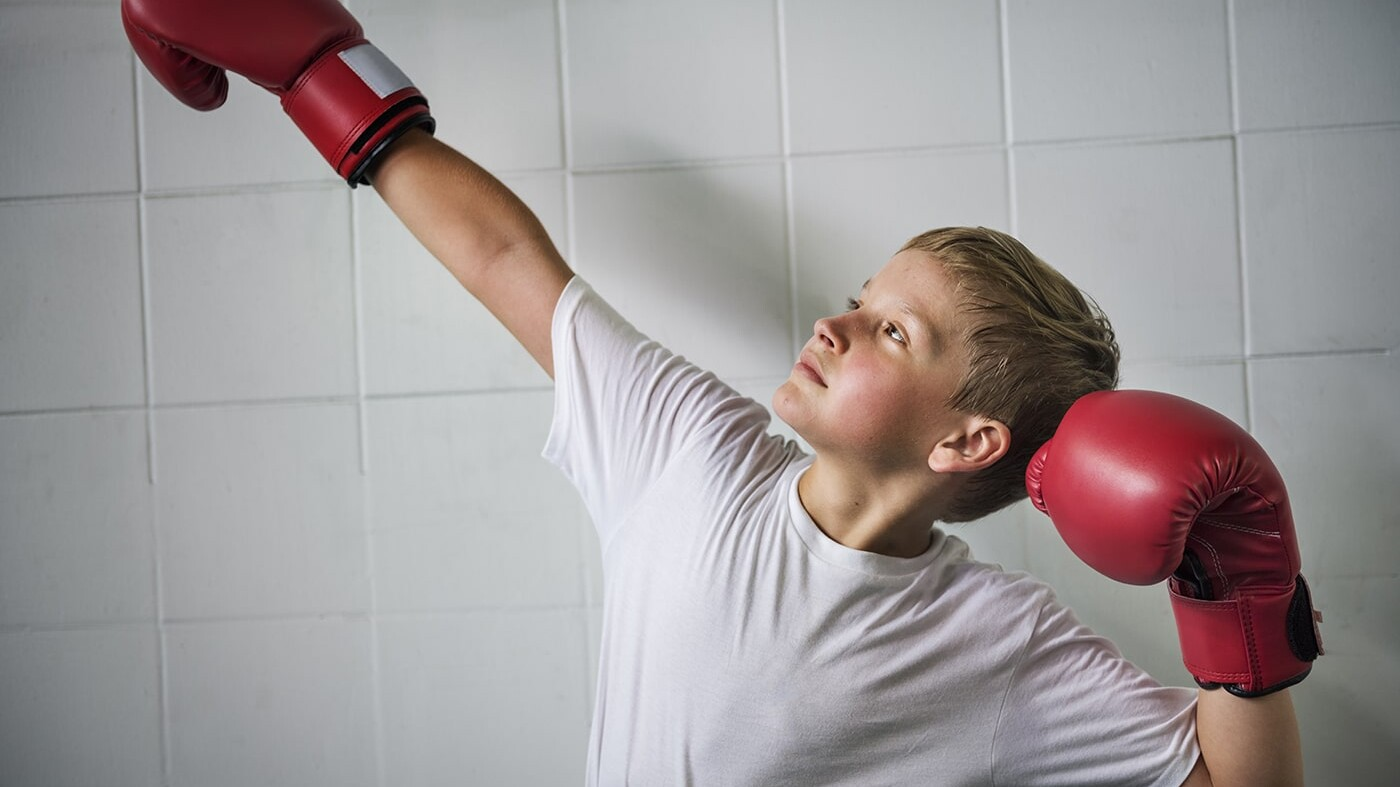 Confident boy posing with boxing gloves