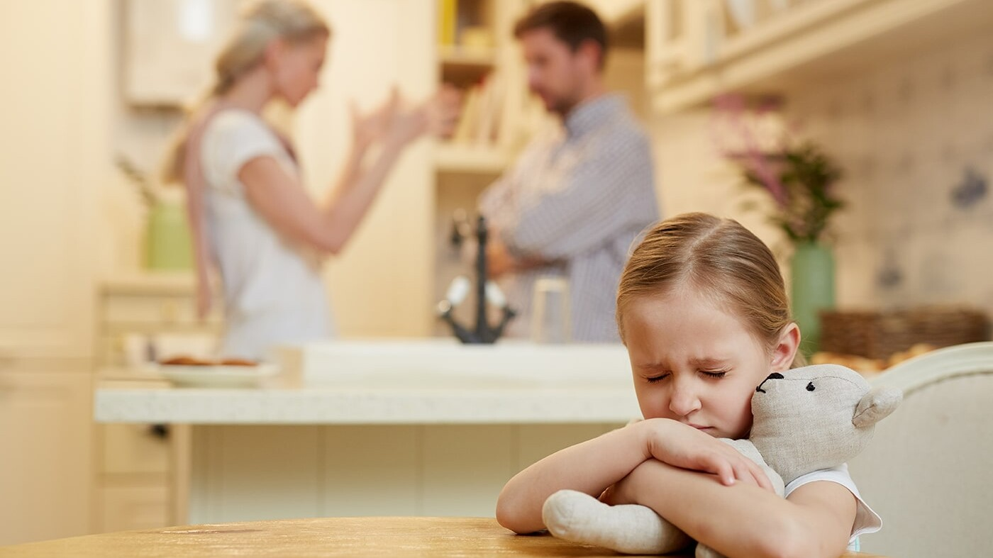 Worried child with parents arguing in background