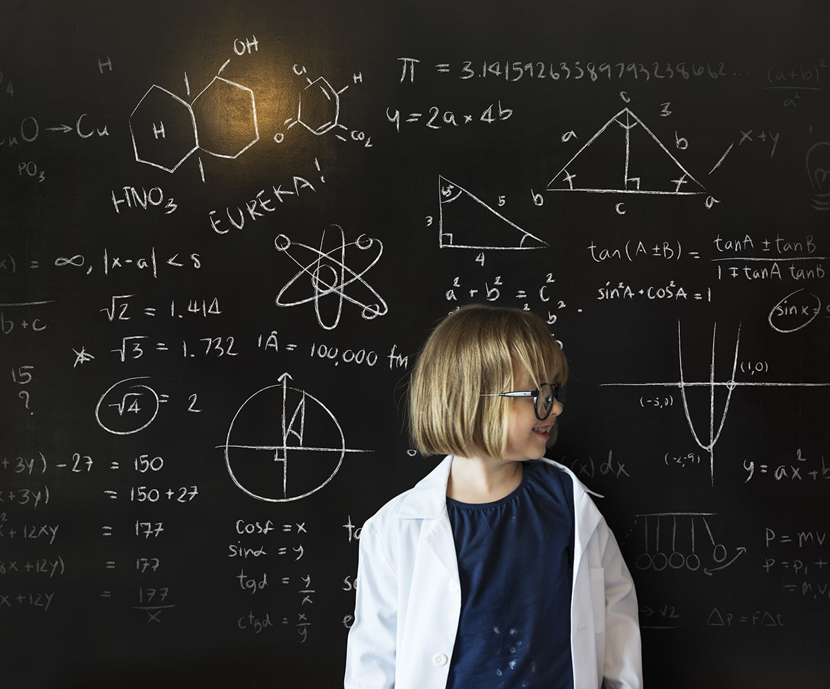 Gifted child in front of blackboard with equations