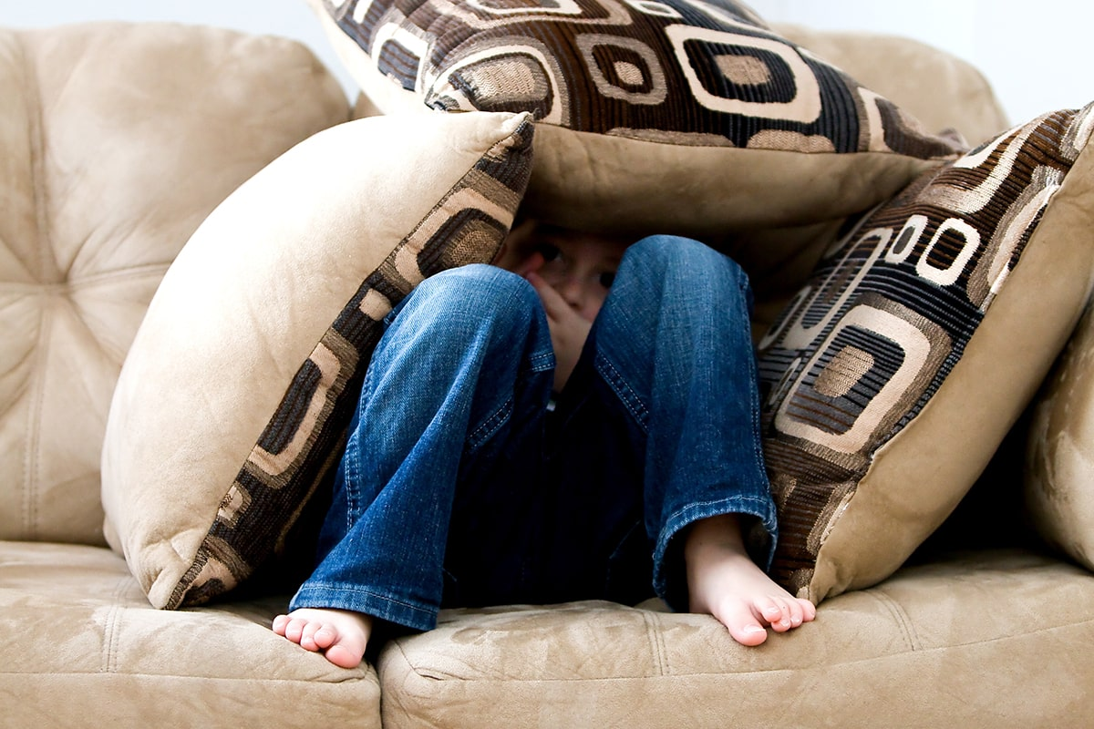 Child hiding in pillow fort